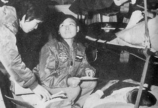 공수되는 부상환자를 보살피는 비행간호장교들